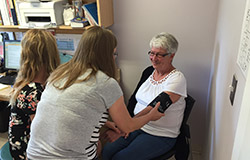 Older woman having her blood pressure taken by younger female practitioner