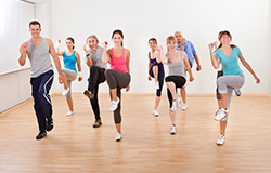 Group of 8 adults (men and women) doing exercises to music