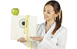 A female dietician holding a scale with a measuring tape wrapped around it and an apple sitting on top