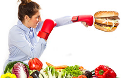 Female with boxing gloves on punching a hamburger.  Various vegetables laid out in front of her