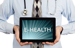 "Doctor holding a computer tablet with the ""E-Health"" promoting electronic health services"